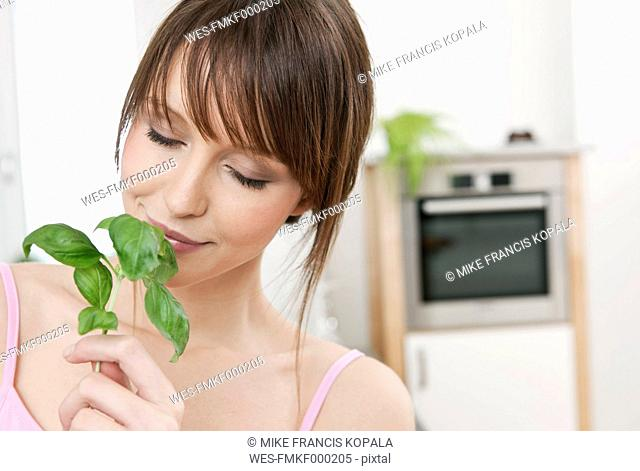 Germany, Cologne, Woman smelling basil