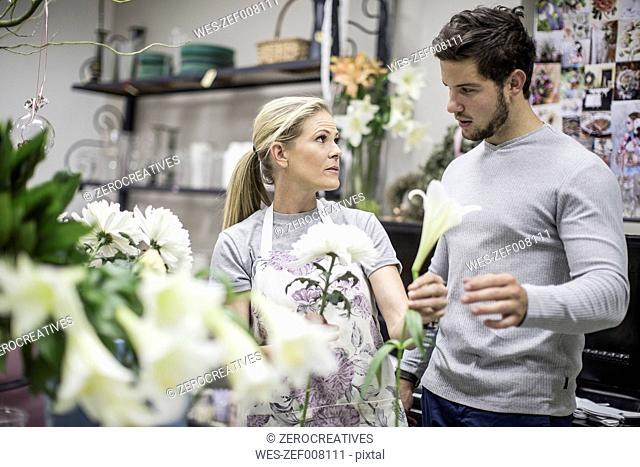Shop assistant in flower shop advising customer