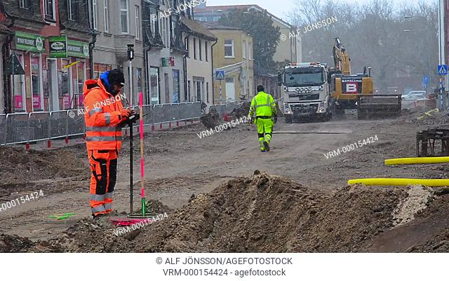 Ingenieer with measuring instrument on construction site