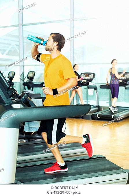 Man drinking water and running on treadmill at gym