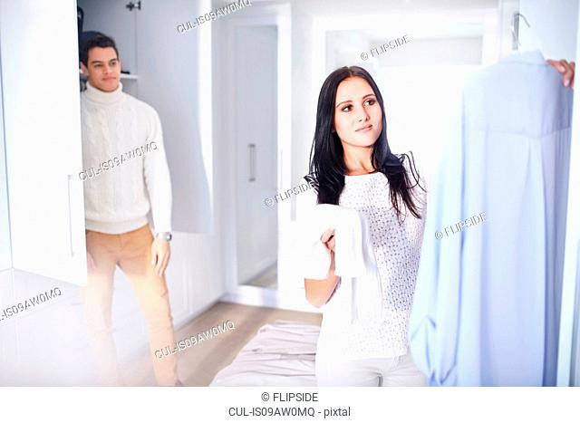 Young woman making decisions whilst getting ready in bedroom