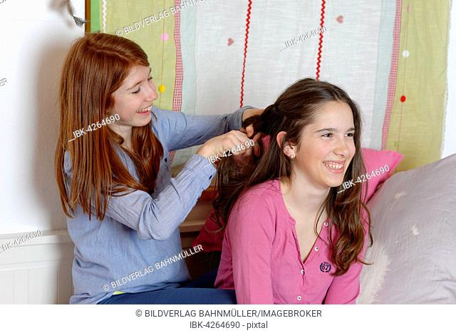 Teenage girls doing each other's hair, plaits, Germany