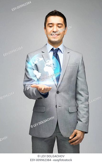 business, people, technology and global communication concept - happy businessman in suit showing globe hologram over gray background