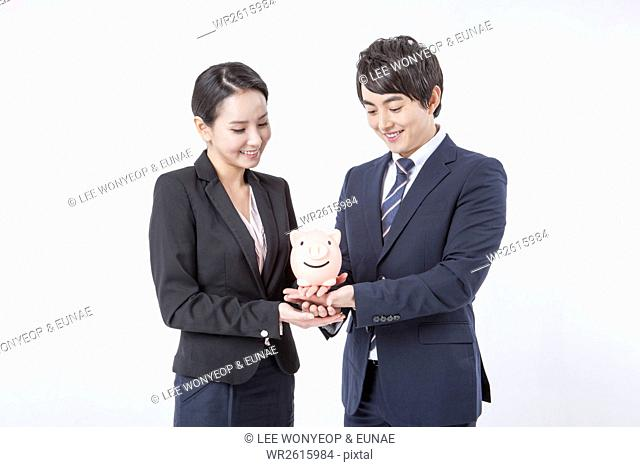 Smiling business people with piggy bank