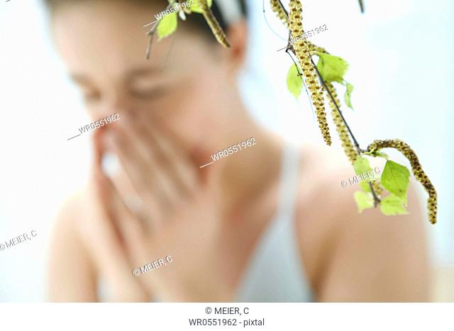 a branch with leaves of a birch tree - in the background blurred a young woman sneezing
