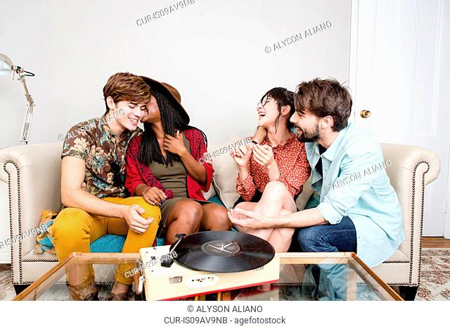 Young hipster couples laughing whilst listening to vinyl music in apartment