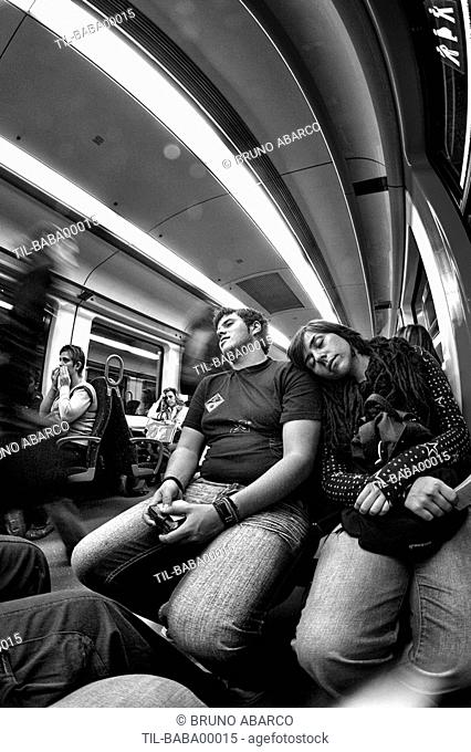 Two young people asleep on a train