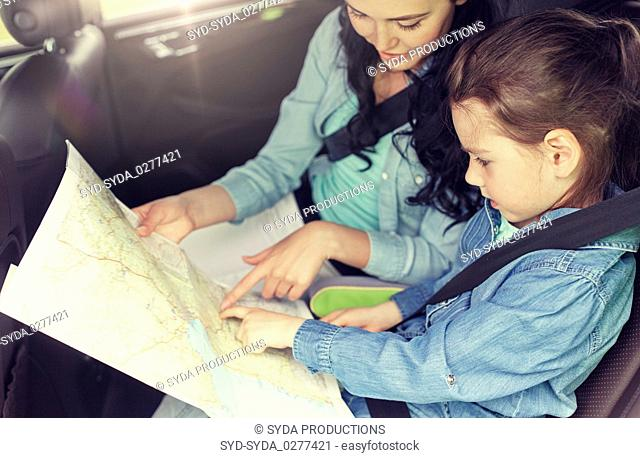 happy family with travel map driving in car