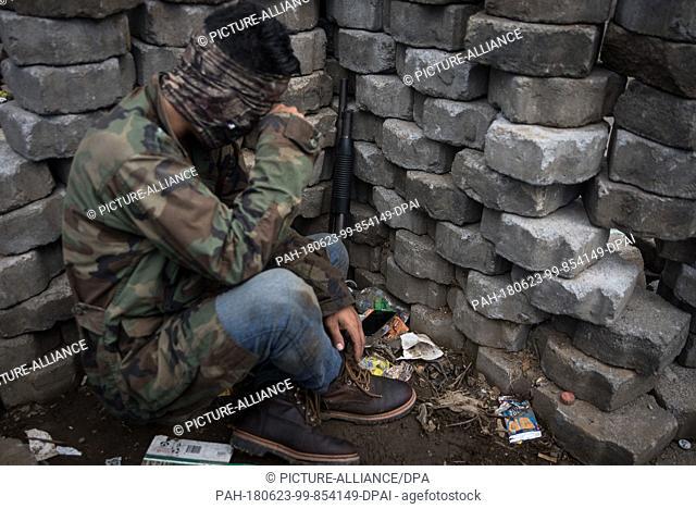 23 June 2018, Nicaragua, Managua: A student cover himself behind a trench. Paramilitaries stormed the National Autonomous Universities of Managua