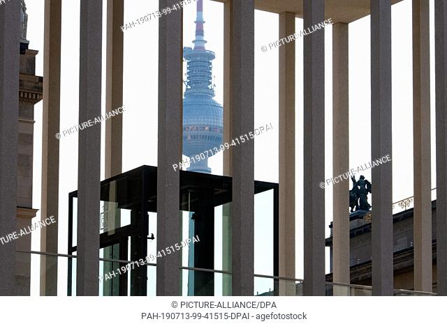 13 July 2019, Berlin: The television tower at Alexanderplatz can be seen behind the struts of the entrance to the James Simon Gallery