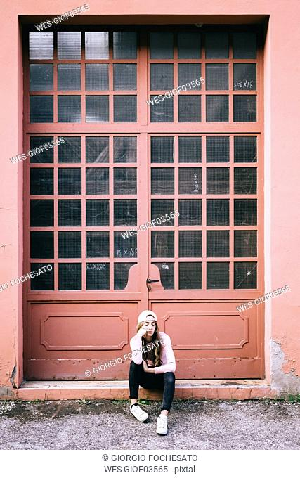 Fashionable young woman sitting in front of entrance gate
