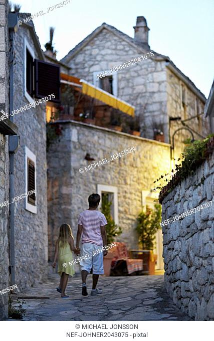 Brother and sister walking together through narrow street