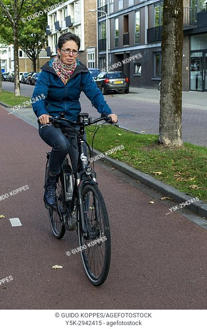 Tilburg, Netherlands. Mature adult caucasian woman and Multiple Sclerosis patient still riding her bike coping with her chronic condition