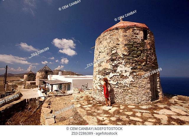 Woman in front of an old windmill, Folegandros, Cyclades Islands, Greek Islands, Greece, Europe