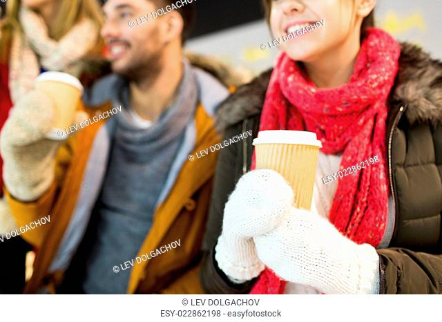 people, friendship, hot drinks and leisure concept - close up of happy friends drinking from paper coffee cups on skating rink