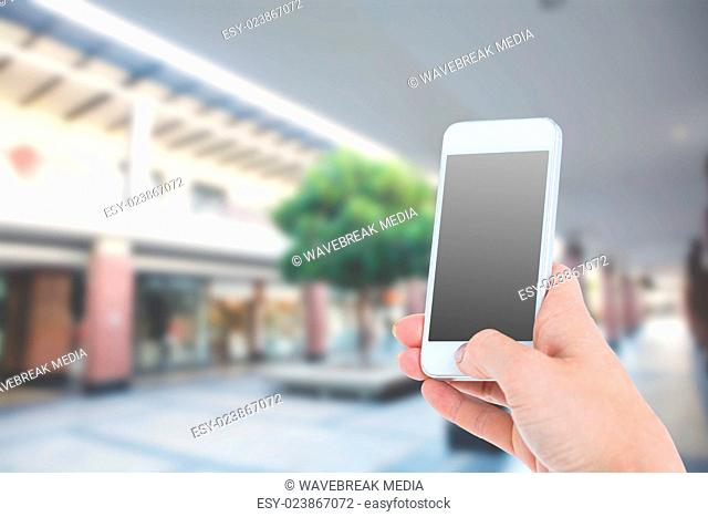 Composite image of woman showing smartphone