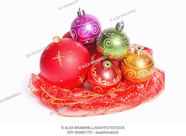 Christmas baubles nestling in a nest of red ribbon with a white background  Studio isolated