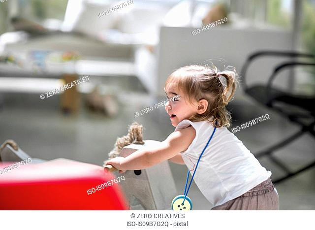 Baby girl with rocking horse