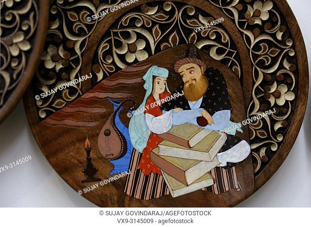 Tashkent, Uzbekistan - May 02, 2017: Hand carved and painted wooden plate in traditional Uzbek style, kept for display in the gallery at Abul Kasim Madrasa