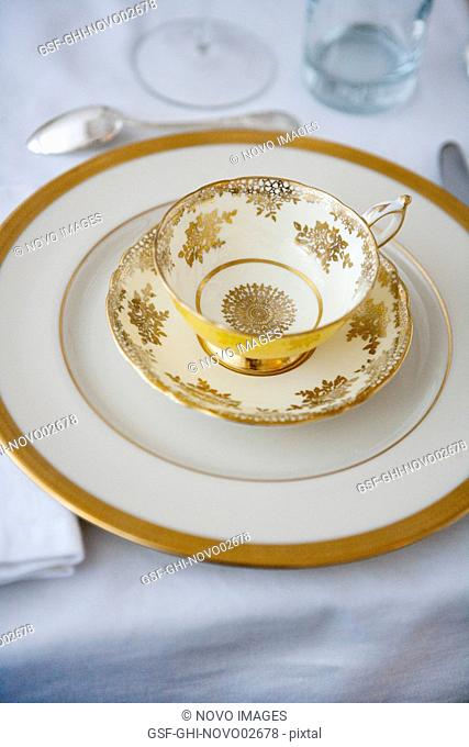 Formal Dining Table Setting with Gold-Accented Teacup and Saucer on Plate with Silverware
