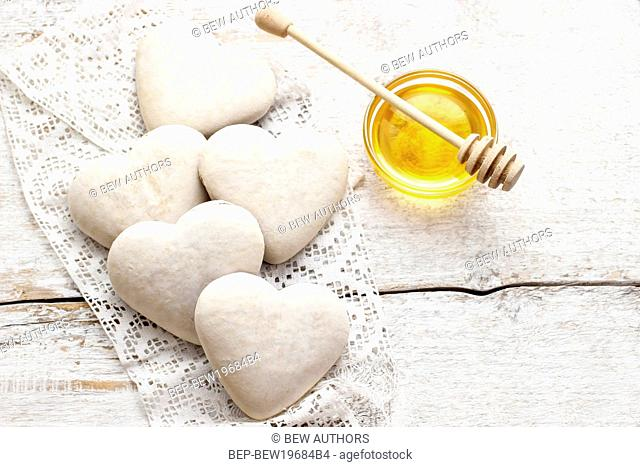 Gingerbread cookies in heart shape on white wooden table. Festive decoration