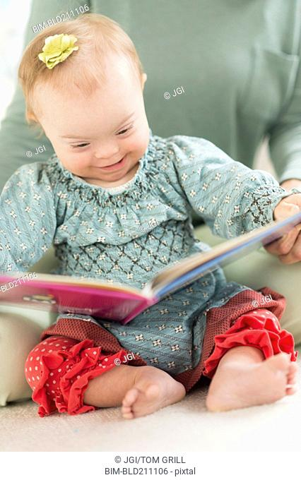 Caucasian baby girl with Down Syndrome reading
