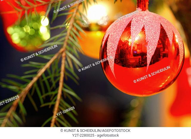 A red bauble is hanging on the Christmas tree