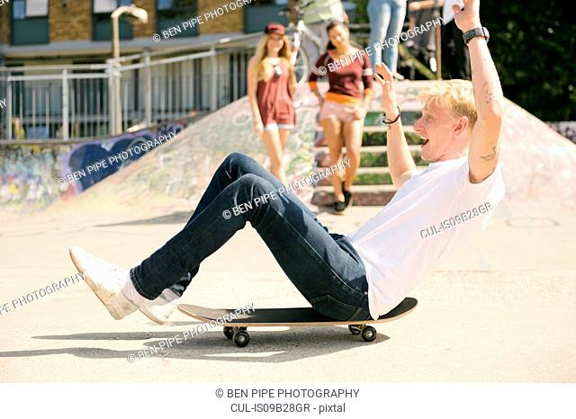 Young male skateboarder sitting on skateboard on the move in city skatepark