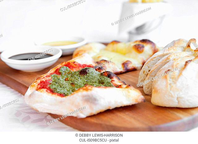 Fresh pizza bread with dipping sauces on chopping board