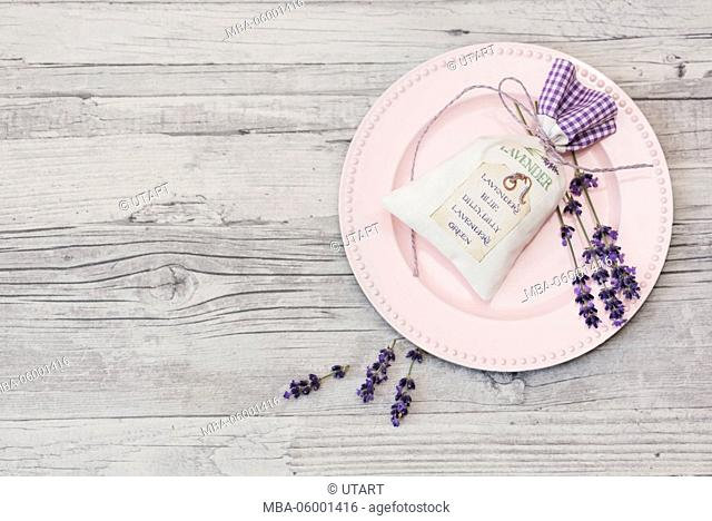 floral still life, pink plate with lavender bag and lavender blossoms on old wooden board