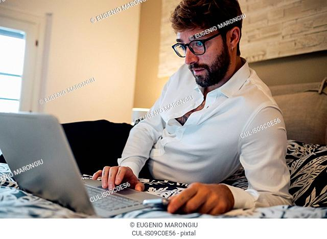 Mid adult man reclining on bed looking at laptop
