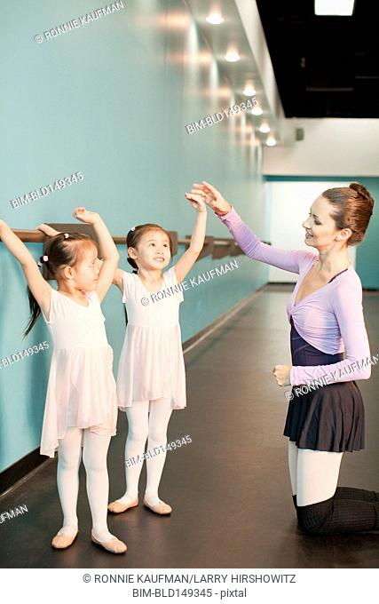 Girls taking ballet lessons from teacher