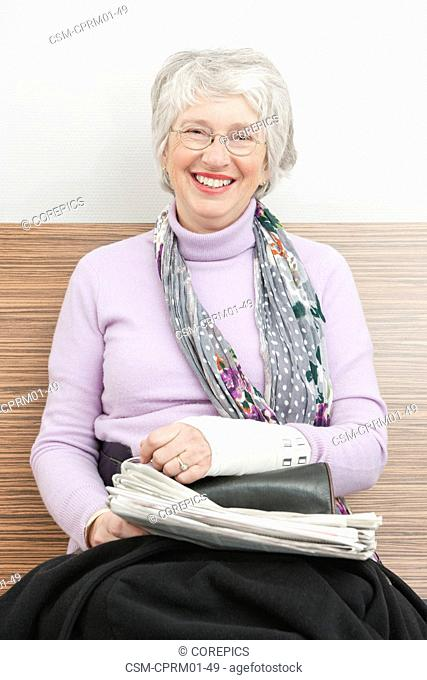 Woman with sprained wrist smiling in the waiting room of a hospital clinic, with a newspaper on her lap
