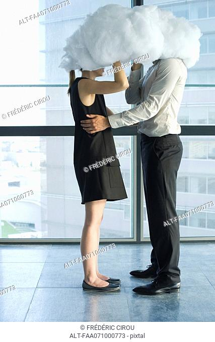 Businessman and businesswoman embracing behind cloud