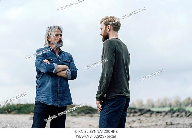 Father and son meeting outdoors, talking together