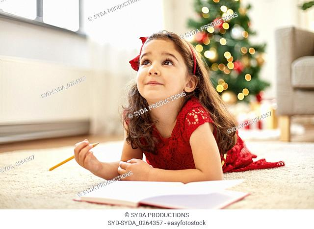 little girl making christmas wish list at home