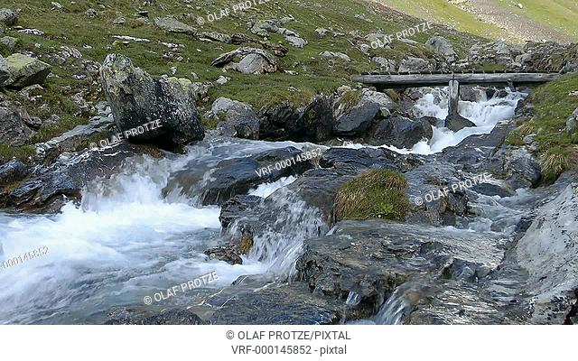 Small water stream in a spring landscape at the Swiss Alps, Switzerland
