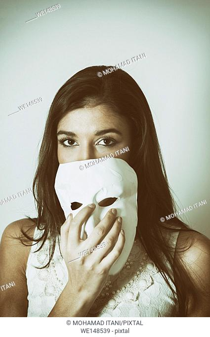 Mysterious young woman holding a white mask in front of her face