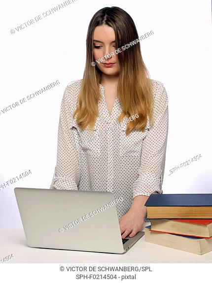 Woman using laptop with books