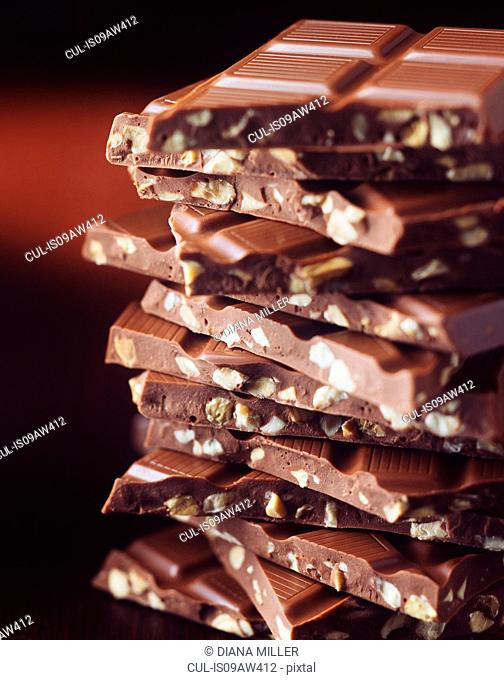 Stack of broken chocolate with hazelnuts, close-up