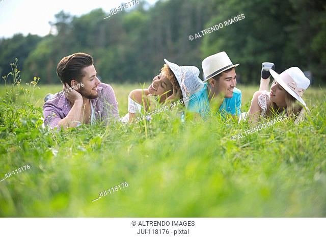 Young Couples Wearing Hats Lying In Summer Field