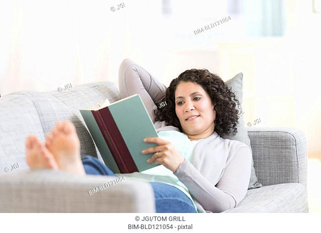 Mixed race woman reading on sofa