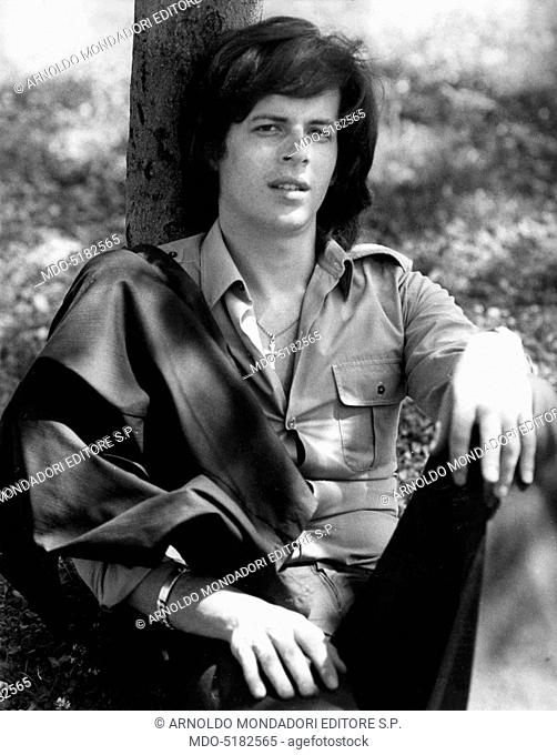 Claudio Baglioni (Claudio Enrico Paolo Baglioni), the Italian singer-songwriter, posing seated in a park, leaning his back against the trunk of a tree