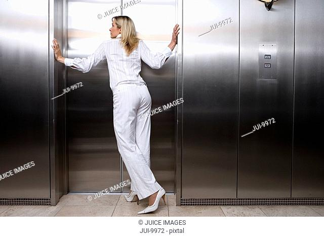 Businesswoman waiting for lift, leaning on walls by door, rear view