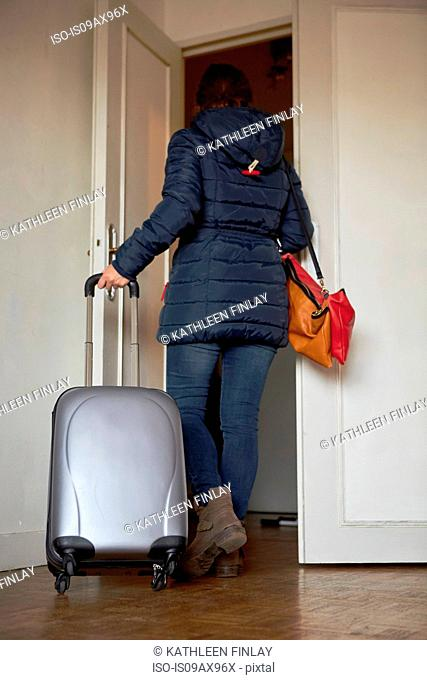 Woman walking out of door with wheeled suitcase, rear view