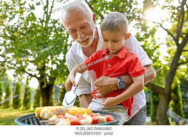 Grandfather helping grandson turning a corn cob during a barbecue in garden