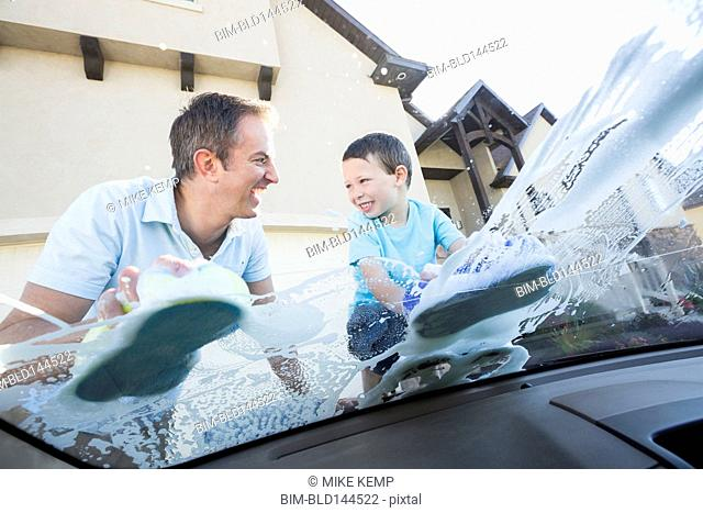Caucasian father and son washing car windshield