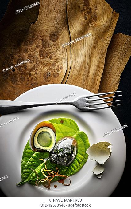 Food art: 100 year egg (Chinese speciality) on a plate on a wooden surface