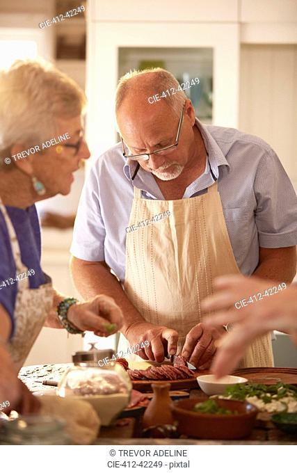Focused senior man slicing salami in cooking class