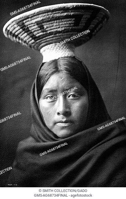 A photographic portrait of a Native American woman, she is shown draped in cloth and has a woven basket on top of her head